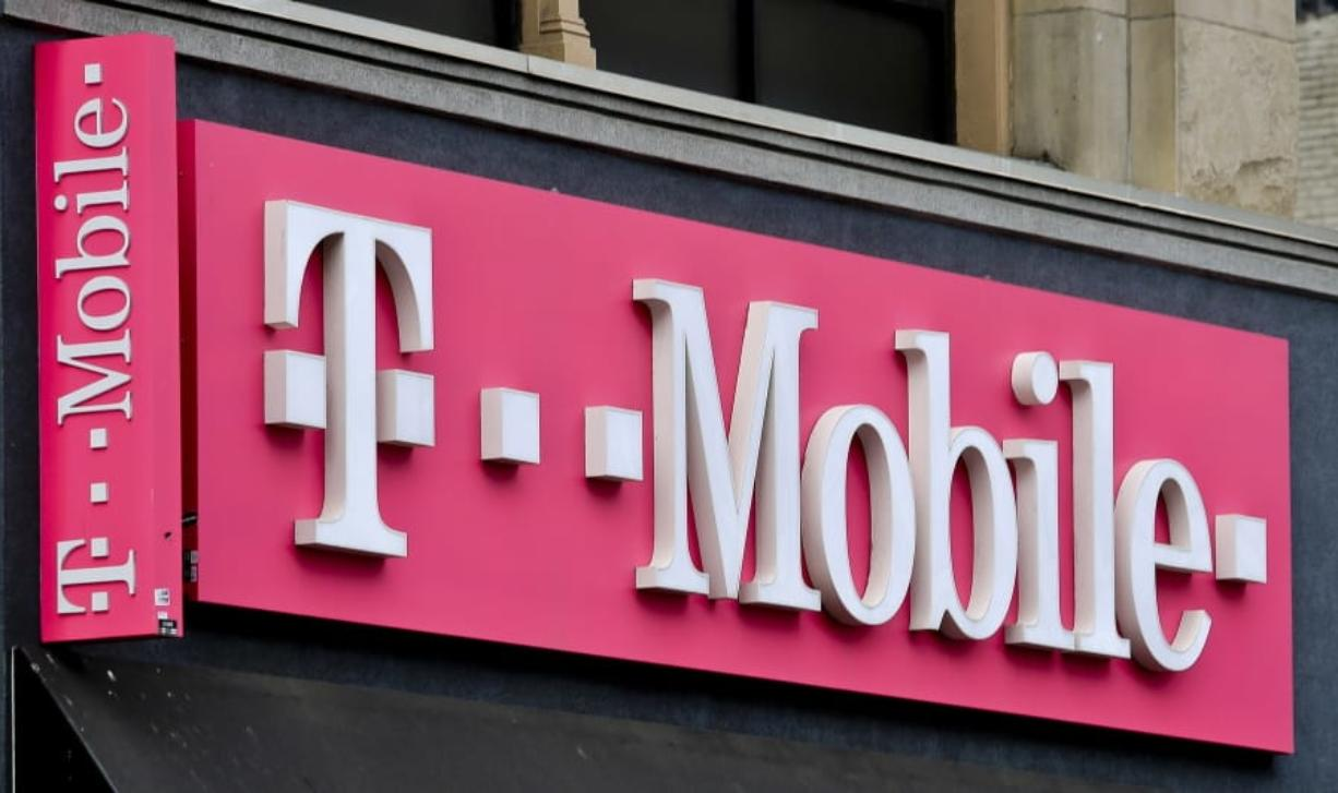 FILE - This April 30, 2018, photo shows a T-Mobile store in Herald Square in New York. T-Mobile promises a new $15 wireless plan and other initiatives if its $26.5 billion Sprint deal goes through. (AP Photo/Bebeto Matthews, File)