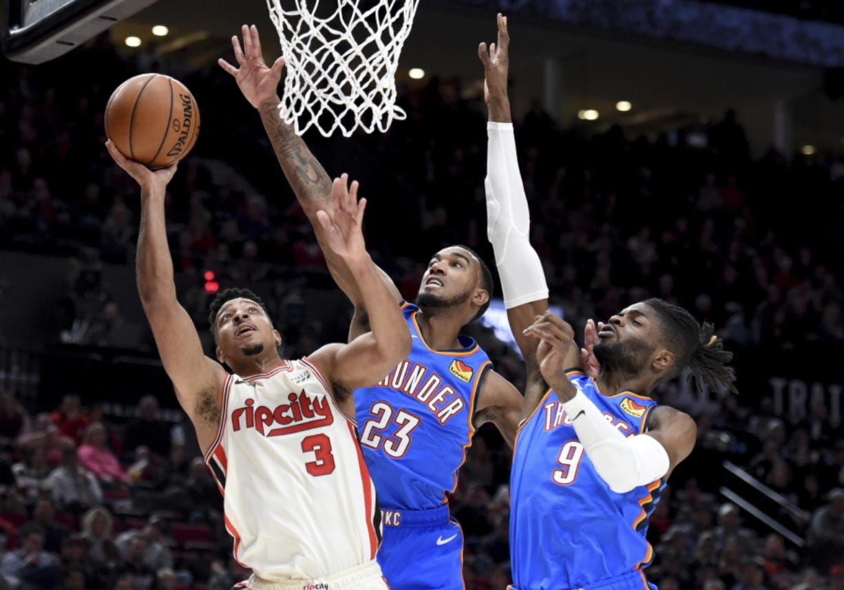 Portland Trail Blazers guard CJ McCollum, left, drives to the basket as Oklahoma City Thunder guard Terrance Ferguson, center, and center Nerlens Noel, right, defend during the second half of an NBA basketball game in Portland, Ore., Wednesday, Nov. 27, 2019. The Blazers won 136-119. (AP Photo/Steve Dykes)