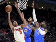 Portland Trail Blazers guard CJ McCollum, left, drives to the basket as Oklahoma City Thunder guard Terrance Ferguson, center, and center Nerlens Noel, right, defend during the second half of an NBA basketball game in Portland, Ore., Wednesday, Nov. 27, 2019. The Blazers won 136-119.