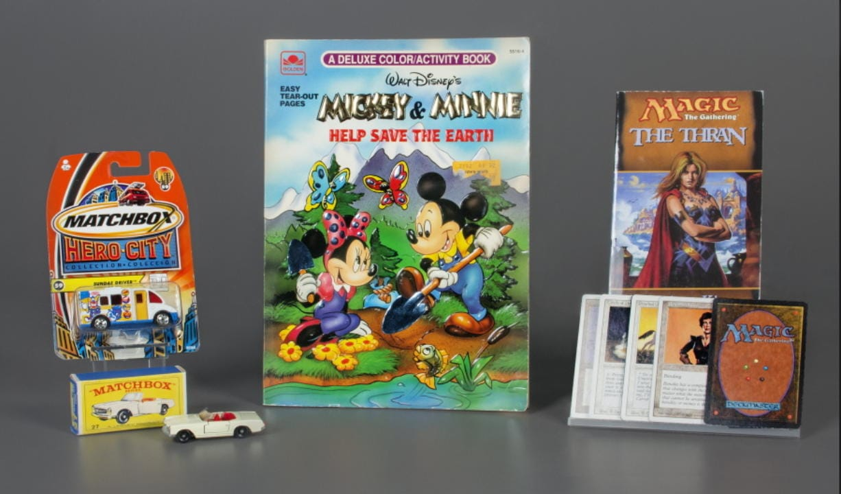 In this Oct. 7, 2019 photo provided by the National Toy Hall of Fame, Matchbox Cars, left, the coloring book, center, and the collectible card game Magic: The Gathering were inducted into the National Toy Hall of Fame in Rochester, N.Y. The winners were selected by a panel of judges from among 12 finalists, which also included: Care Bears, Fisher-Price Corn Popper, Jenga, Masters of the Universe, My Little Pony, Nerf Blaster, Risk, the smartphone and the top. (Victoria Gray/The Strong, National Toy Hall of Fame via AP)