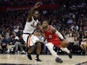 Portland Trail Blazers' Damian Lillard (0) dribbles next to Los Angeles Clippers' Kawhi Leonard (2) during the first half of an NBA basketball game Thursday, Nov. 7, 2019, in Los Angeles.