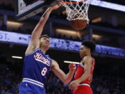 Sacramento Kings guard Bogdan Bogdanovic, left, dunks next to Portland Trail Blazers guard Anfernee Simons during the first quarter of an NBA basketball game in Sacramento, Calif., Tuesday, Nov.