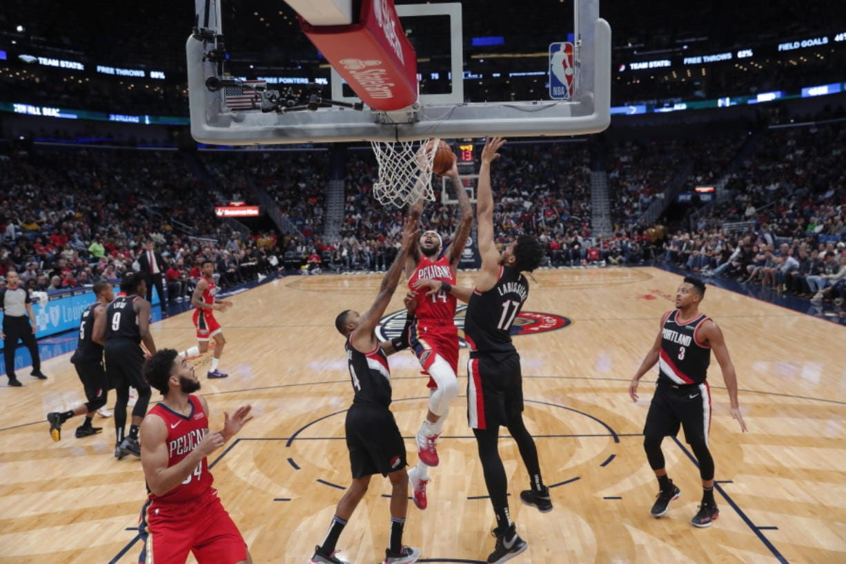 New Orleans Pelicans forward Brandon Ingram (14) goes to the basket between Portland Trail Blazers forward Skal Labissiere (17) and guard Kent Bazemore in the second half of an NBA basketball game in New Orleans, Tuesday, Nov. 19, 2019. The Pelicans won 115-104. (AP Photo/Gerald Herbert)