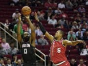 Houston Rockets' James Harden (13) shoots as Portland Trail Blazers' Rodney Hood (5) defends during the first half of an NBA basketball game Monday, Nov. 18, 2019, in Houston. (AP Photo/David J.