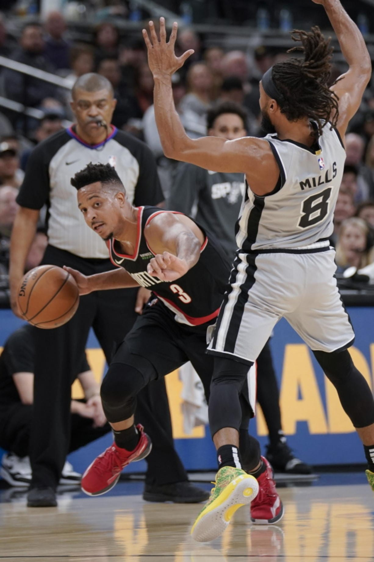 Portland Trail Blazers' C.J. McCollum (3) is called for an offensive foul after colliding with San Antonio Spurs' Patty Mills during the first half of an NBA basketball game, Saturday, Nov. 16, 2019, in San Antonio.