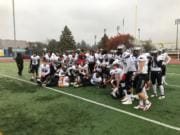 Union players pose for photos following a 42-6 win over Mount Rainier in a 4A district crossover game on Saturday at Highline Memorial Stadium in Burien.