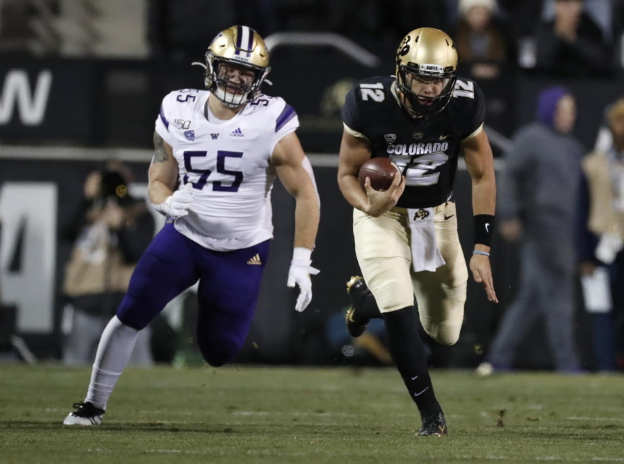 Colorado quarterback Steven Montez runs for a short gain as Washington linebacker Ryan Bowman pursues during the first half of an NCAA college football game Saturday, Nov. 23, 2019, in Boulder, Colo.
