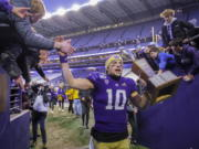Washington quarterback Jacob Eason high fives fans as he leaves the field with the Apple Cup after an NCAA college football game against Washington State, on Friday, Nov. 29, 2019 in Seattle. Washington won 31-13.