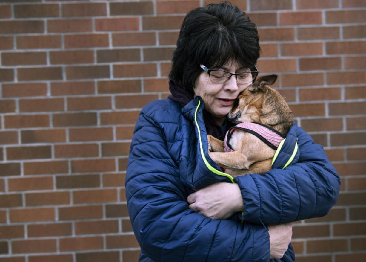 """Longview resident Roxanne Ponn snuggles her chihuahua """"Pooh,"""" who was found Monday after fleeing from a house fire a week earlier. (Courtney Talak/The Daily News) (Courtney Talak/The Daily News)"""