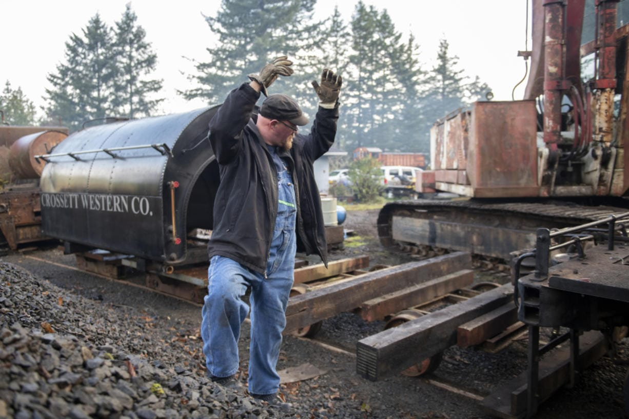Matt Barton, vice president of the Chelatchie Prairie Railroad Association, signals that the engineer inching a locomotive along is running out of clear track. Behind Barton is the saddle-style water tank that was lifted off the group's 1929 steam engine during the federally mandated inspection. (Zach Wilkinson for The Columbian)