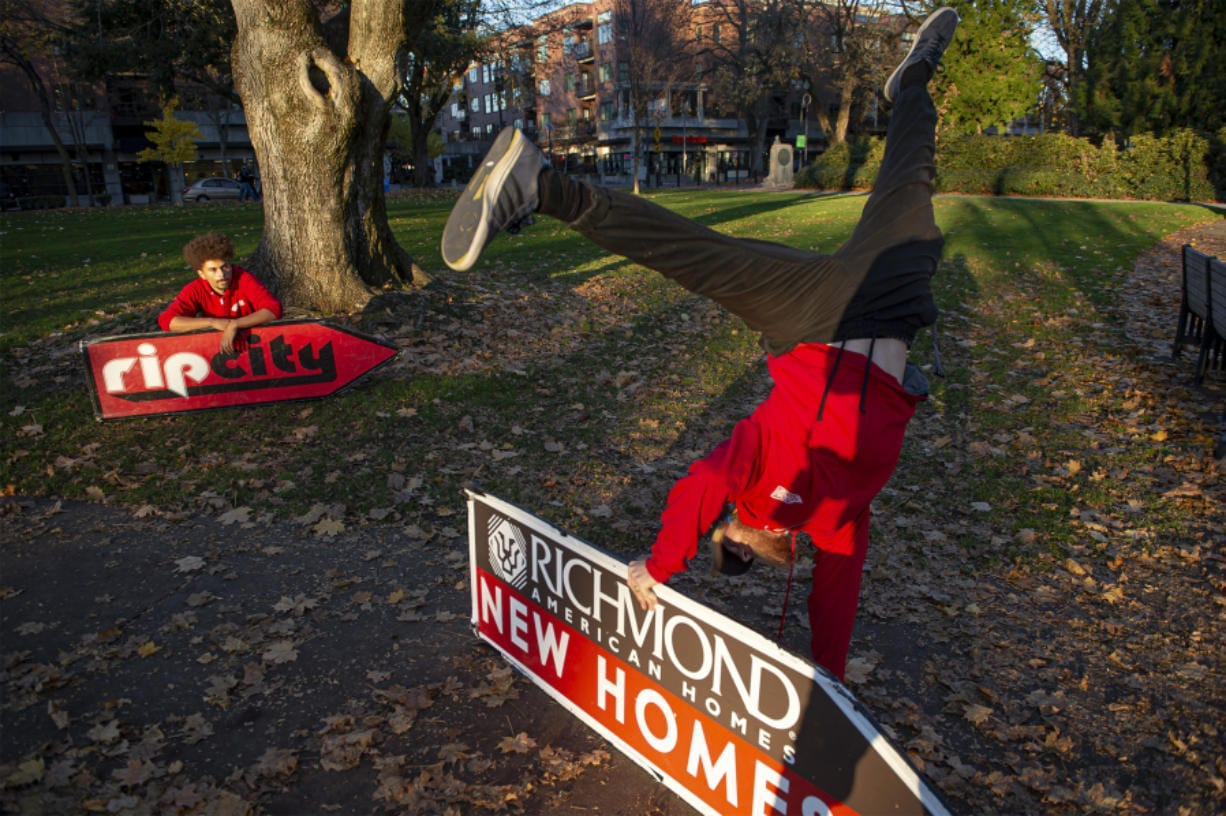 Sign spinner Jeremiah Zueger, left, and Chance Jordan, general manager of AArrow Sign Spinners practice in Esther Short Park in Vancouver on a recent November afternoon.