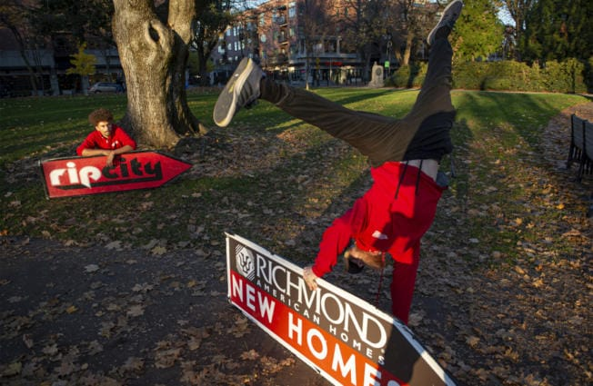 Sign spinner Jeremiah Zueger, left, and Chance Jordan, general manager of AArrow Sign Spinners practice in Esther Short Park in Vancouver on a recent November afternoon. (Nathan Howard/The Columbian)