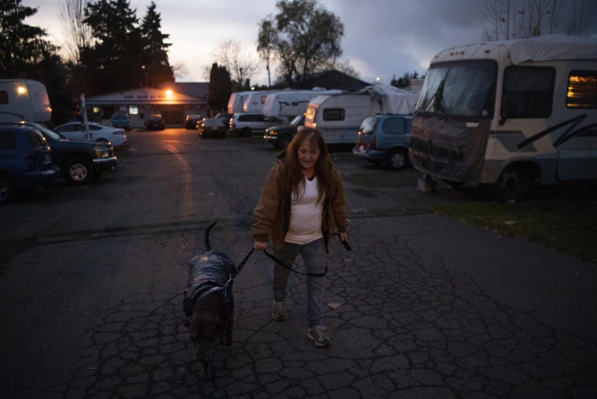 Lori Cuevas walks her dog up to the entrance of Sam's Good RV Park on Highway 99 in Hazel Dell on Nov. 25. She said she doesn't want to move from the park where she's lived for about 13 years.