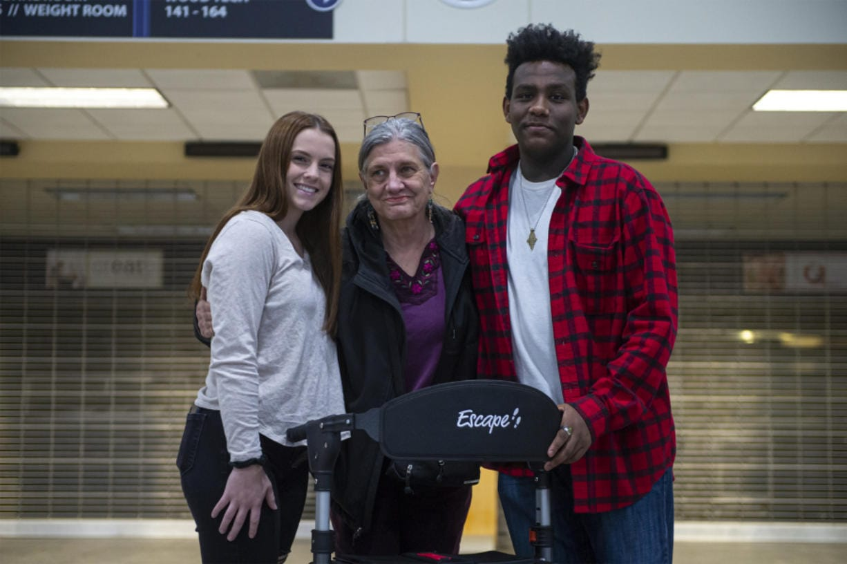 Hayley Oja, from left, Arlene Rose and Musse Barclay at Hockinson High School with a new walker Rose purchased with money raised by two of her students. Rose is a substitute teacher who has a rare neurological disease that inhibits her ability to walk. The students raised money to help her purchase a walker and a wheelchair.