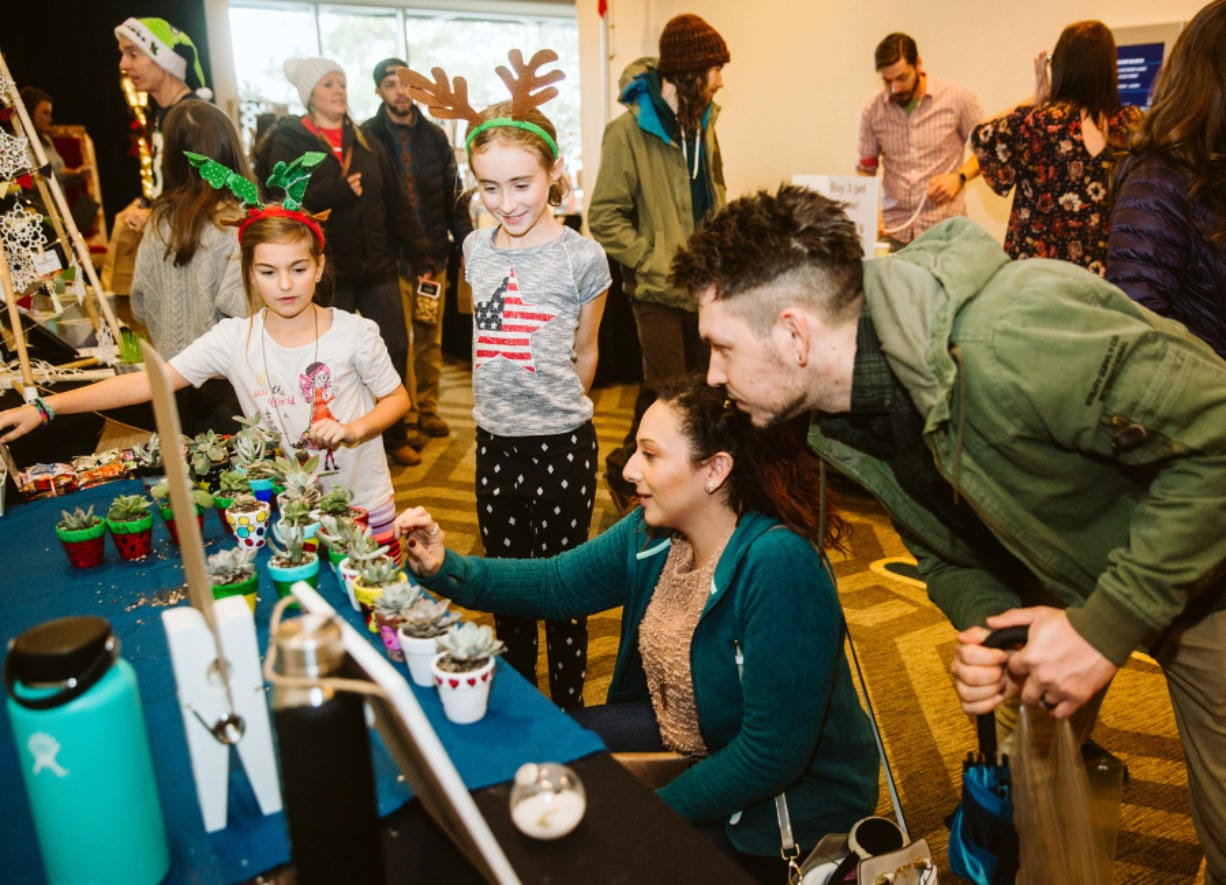 Sophia Campbell, 7, of Portland, and Emily Corsen, 9, of Vancouver, talk to Samantha Duenas, of Los Angeles, and Aaron Ferrara, of Vancouver, about the succulents and hand-painted pots they have for sale on Sunday during the Vancouver Farmers Market Holiday Market at the Hilton Vancouver Washington. (Roberto Rodriguez for The Columbian)