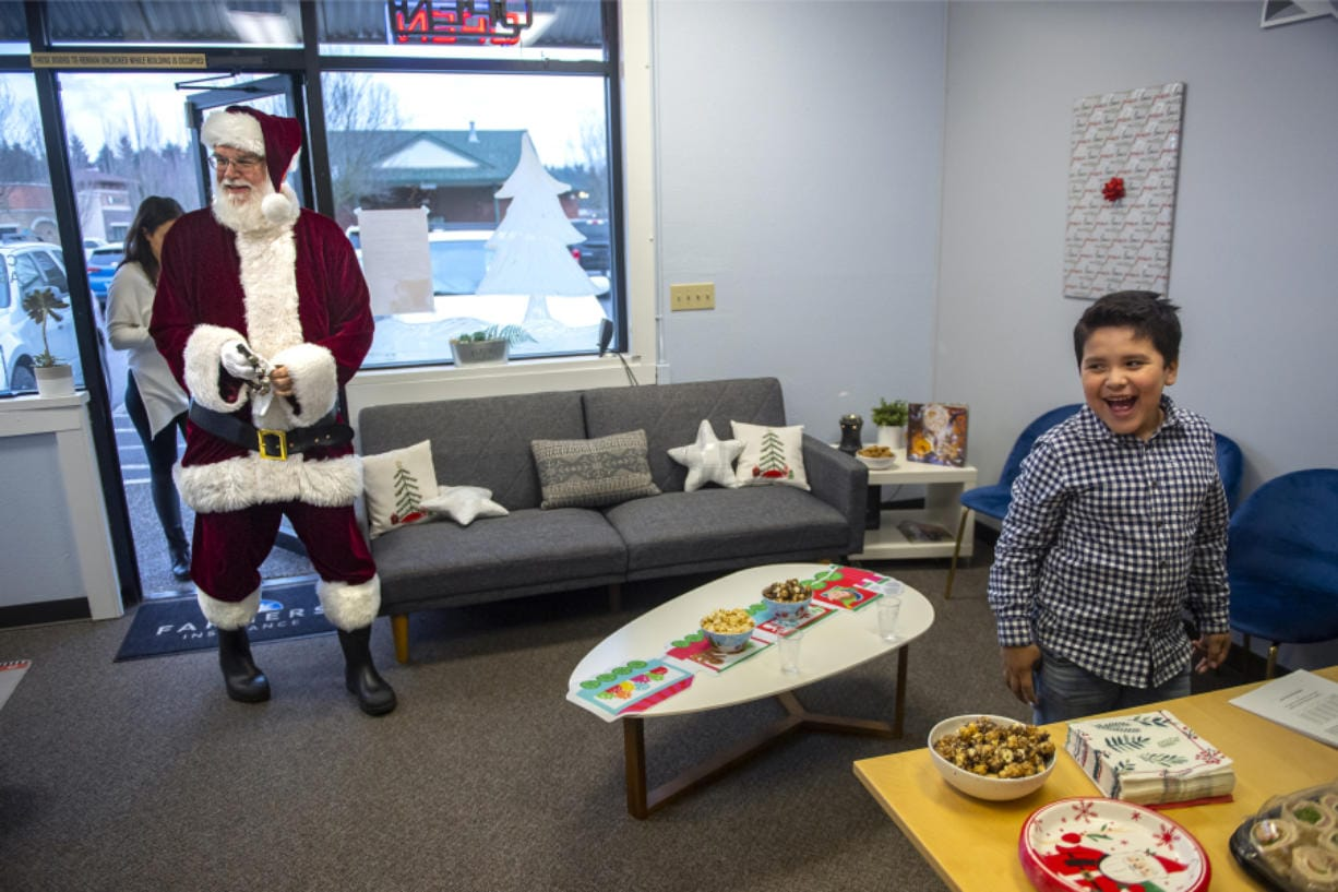 Santa Claus, played by Ted Mach of Battle Ground, walks into Farmers Insurance in Salmon Creek as Owen Sanchez-Jauregui, 7, reacts to seeing him Wednesday. (Photos by Nathan Howard/The Columbian)