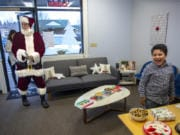 Santa Claus, played by Ted Mach of Battle Ground, walks into Farmers Insurance in Salmon Creek as Owen Sanchez-Jauregui, 7, reacts to seeing him Wednesday.