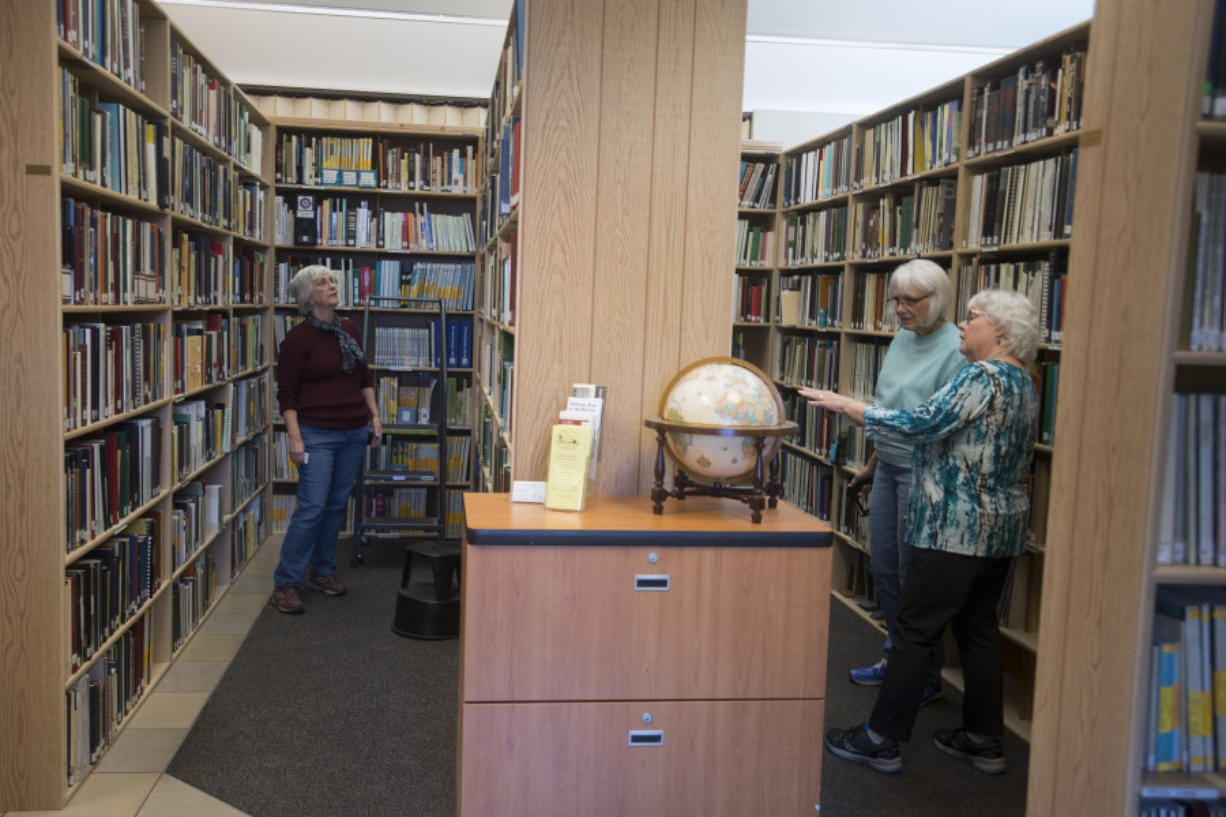 Marcia Grubb, from left, education director for the Clark County Genealogical Society, looks through books in the library of the organization's new facility with volunteers Sharon Cleveland and Barbara Schrag on Thursday. (Photos by Amanda Cowan/The Columbian)