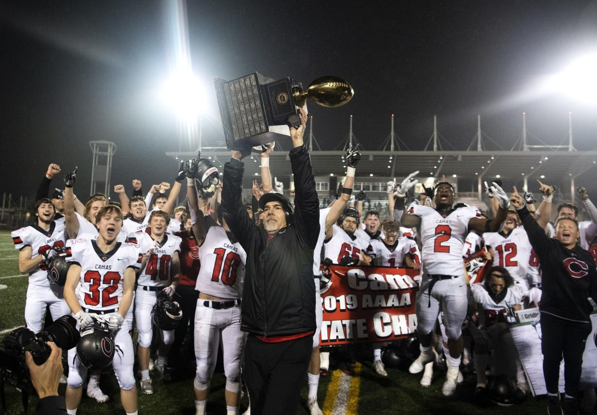 Camas head coach Jon Eagle hoists the trophy into the air after SaturdayÕs win in the Class 4A state championship game against Bothell at Mount Tahoma High School in Tacoma on Dec. 7, 2019.