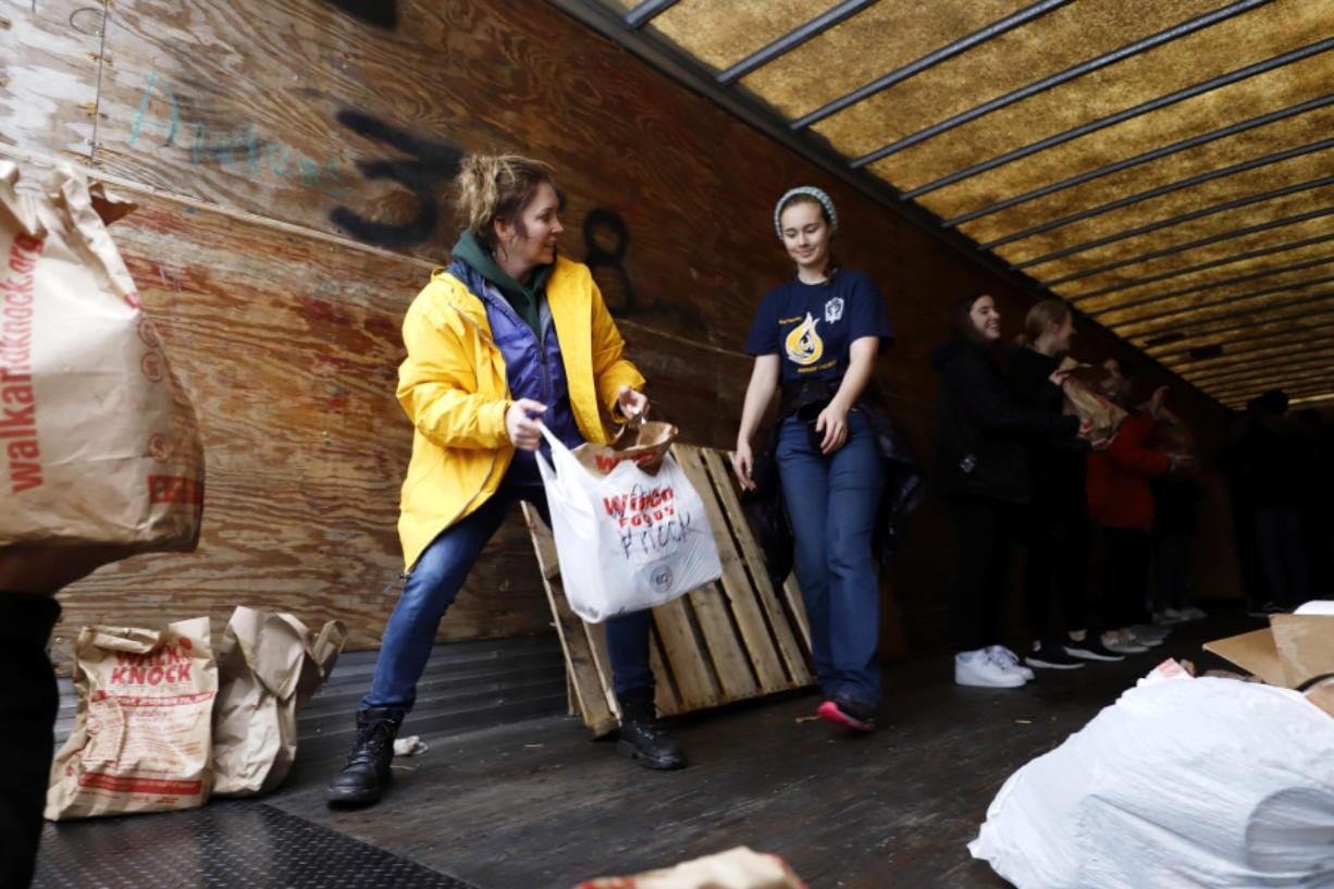 Roxie Olsen, left, passes donated food to Ali Parmenter during the Walk & Knock food drive on Saturday at Chuck's Produce. Olsen previously served as a Walk & Knock board member for 15 years. Now, she continues to volunteer.