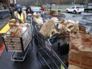 Marge Boulden, left, helps unload donated food at Chuck's Produce during the annual Walk & Knock food drive.