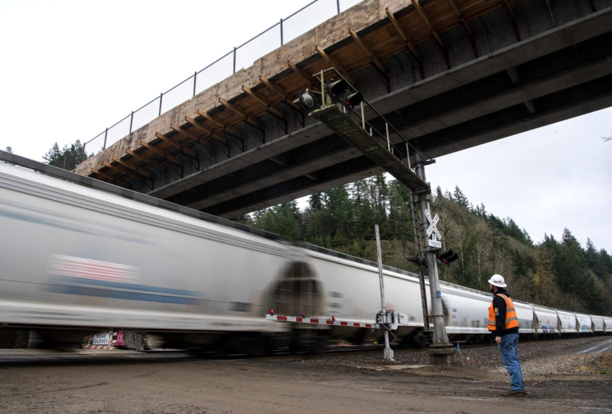 Mick Cannon, a superintendent for Ceccanti Inc. of Tacoma, waits for a fast-moving train before Monday's opening of a concrete bridge spanning the railroad tracks and Lake River at the Ridgefield National Wildlife Refuge.