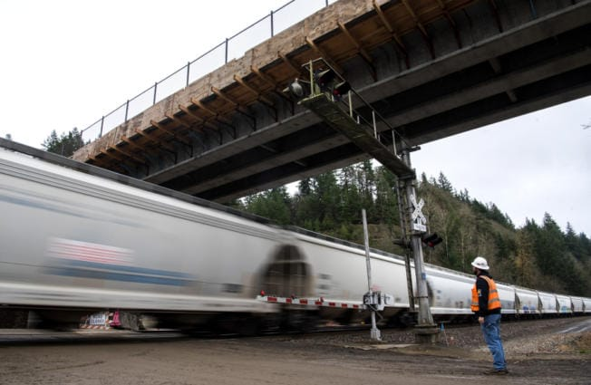 Mick Cannon, a superintendent for Ceccanti Inc. of Tacoma, waits for a fast-moving train before Monday's opening of a concrete bridge spanning the railroad tracks and Lake River at the Ridgefield National Wildlife Refuge. (Photos by Alisha Jucevic/The Columbian)