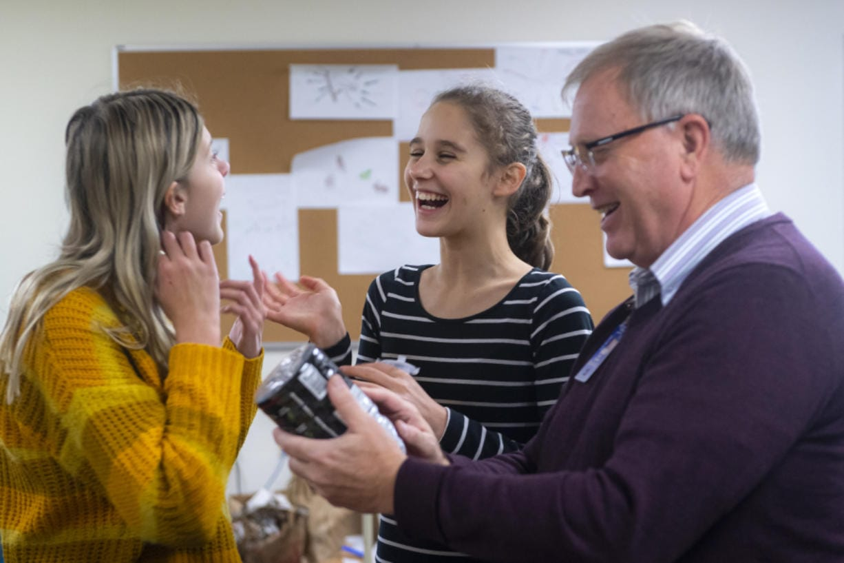 Ella Galloway, 12, from left, Joanna Sokolova, 12, and problems-based learning teacher Kent Graham talk about using a plastic bottle as a building while creating a model of a city with a futuristic water filtration system Friday afternoon at River HomeLink. (Photos by Nathan Howard/The Columbian)