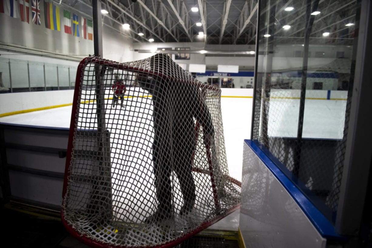 Brennan Bloemke carries hockey nets off the ice before resurfacing the rink at Mountain View Ice Arena. (Photos by Nathan Howard/The Columbian)