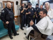 Camas police Officer Carlos Gonzalez, seated, reacts to his new mustache with other members of the Camas police force during a beard shaving fundraiser at Camas Barbershop on Wednesday. Cops in the department grew out their beards during No Shave November, and teamed with the barbershop to raise money on Wednesday for www.zerocancer.org, a nonprofit looking to end prostate cancer.