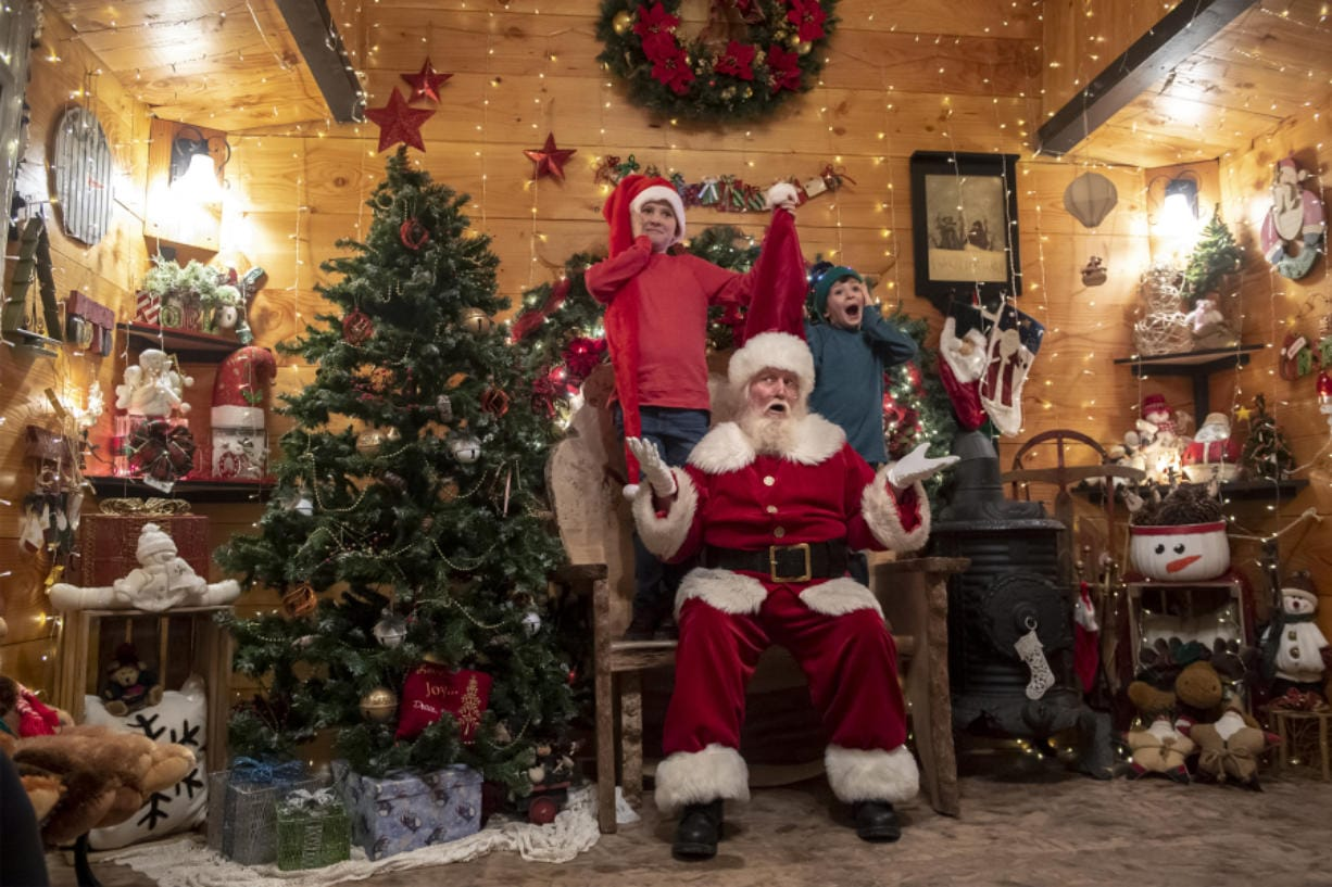 Connar Williams, 11, from left, Santa Claus, played by Brian Trembley, and Gage Williams 6, pose for a photo in Trembley's Santa Chalet in Woodland.