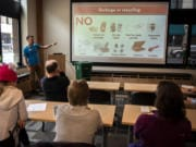 Vancouver Public Works AmeriCorps member Shane Carter discusses items that are not compostable during a lunch-and-learn class offered by Vancouver's solid waste department at Columbia Bank's Community Room in Vancouver.