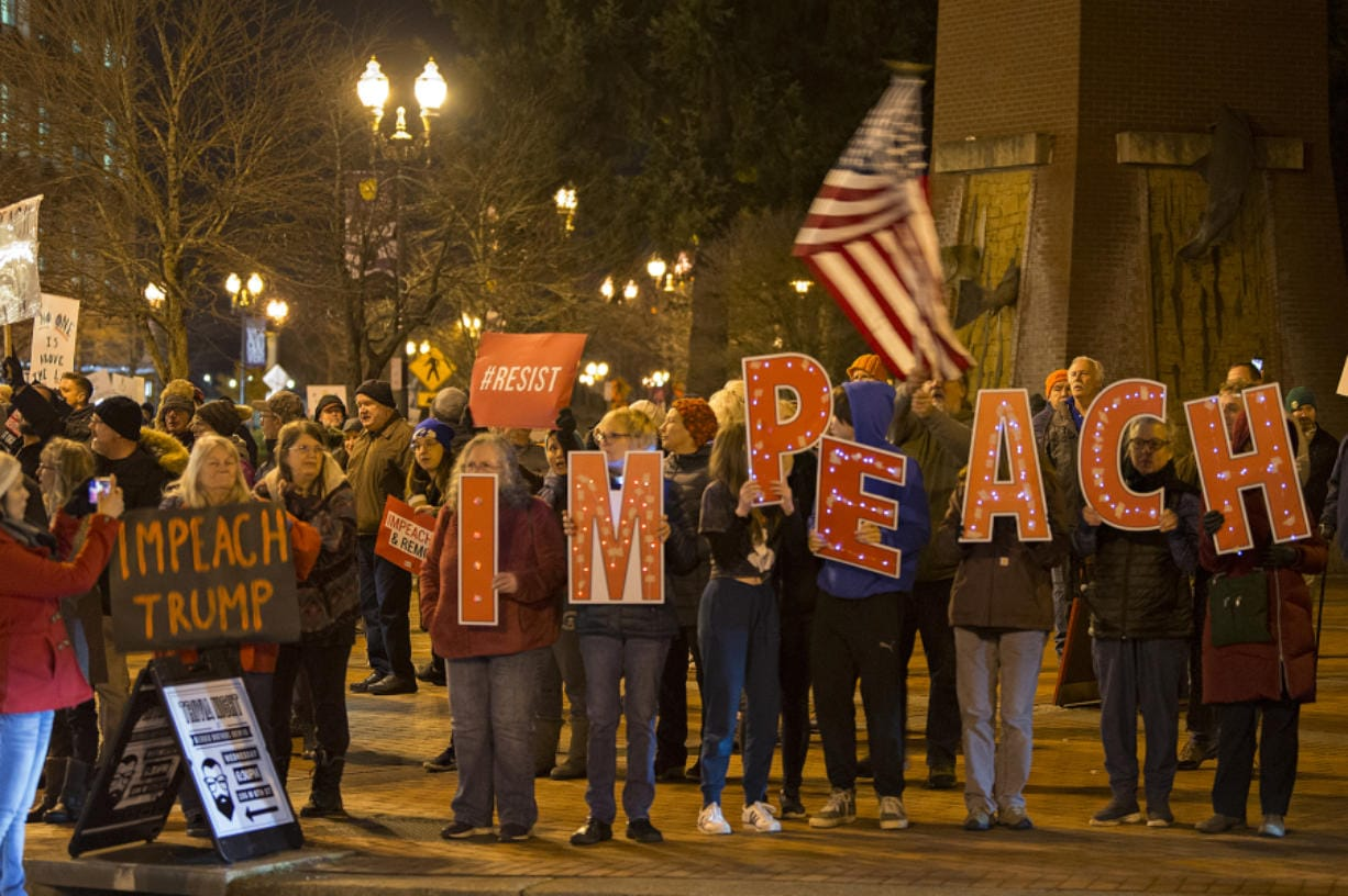 Demonstrators gather to support the impeachment of President Donald Trump during a rally at Esther Short Park on Tuesday evening. Participants kicked off the event with music and chants before hearing from speakers and waving signs along Sixth and Columbia streets. (Amanda Cowan/The Columbian)