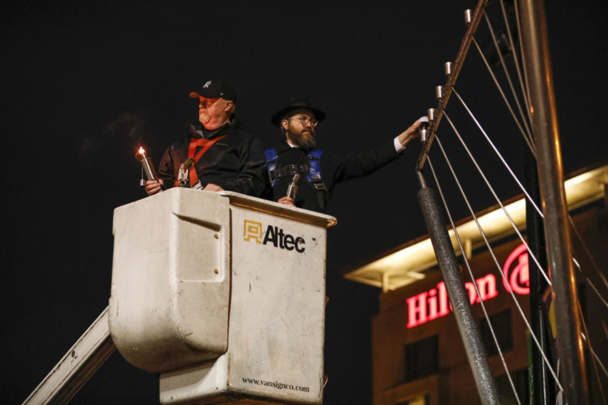 Rabbi Shmulik Greenberg lights a menorah to mark the first night of Hanukkah at Esther Short Park.