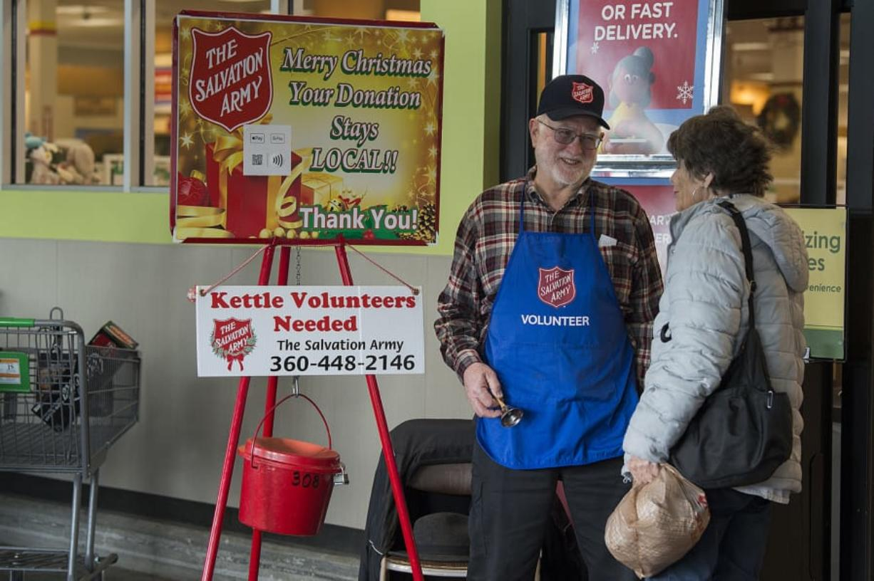 "Bruce Davis of Vancouver, left, greets shopper Myrna Webb of Redmond, Ore., while bell ringing at the Grand Central Fred Meyer on Monday afternoon. Davis has been helping out as a bell ringer for the last 50 years. ""It's actually a lot of fun. I enjoy it,"" he said."