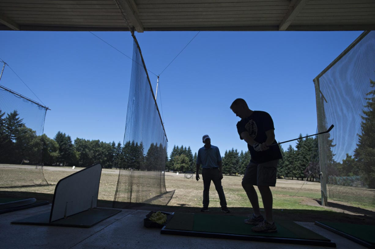 PGA teaching professional Jack Young, left, works with Vancouver resident Slade Langlois while giving him a few helpful tips at Vanco Golf Range on July 26. The city-owned range site is part of the redevelopment area for the Heights District project, and Vanco owner Chuck Milne had previously announced a plan to close the range at the end of 2020. A new lease agreement with the city will now allow the range to operate through 2024.