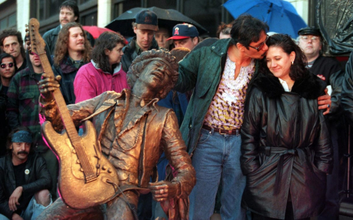 Leon Hendrix kisses his sister, Janie Hendrix, at the 1997 unveiling of a statue of their brother Jimi Hendrix on Capitol Hill. The statue is on permanent display at the intersection of Broadway Avenue and Pine Street. (Benjamin Benschneider/Seattle Times files)