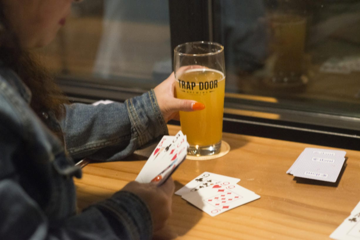 Jean Figueroa takes a drink break while playing gin rummy during a release event for MightyHighPA, a collaborative beer by Wingman Brewing, Boundary Bay Brewing and Trap Door Brewing, at Trap Door's taproom in Vancouver in October 2018. MightyHighPA is the first cannabis terpene beer produced and canned in Washington. Oregon has ruled that it will not allow cannabis-infused alcoholic beverages. (The Columbian files)