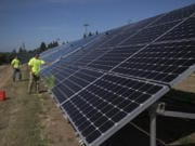 Nick Neathamer, left, and Rafer Stromme, members of the student grounds crew, clean solar panels at Clark Public Utilities in August. The panels need to be cleaned to remove dust to maximize energy production.