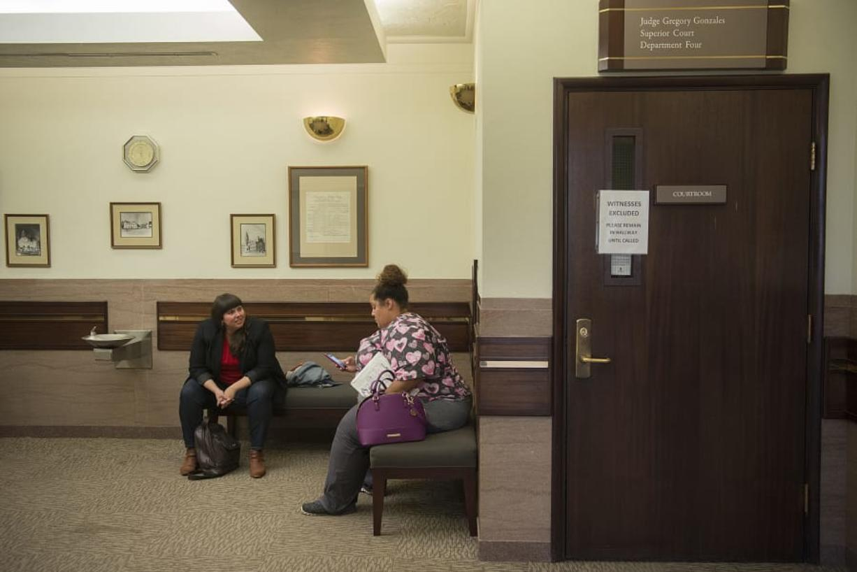 Kate Dunphy, left, deputy director of the Tenants Union of Washington, works with Charmaine Crossley following a hearing in her eviction case at Clark County Courthouse in October 2017.
