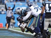 Seattle Seahawks running back Chris Carson scores a touchdown while Carolina Panthers outside linebacker Shaq Thompson (54) tackles during the second half of an NFL football game in Charlotte, N.C., Sunday, Dec. 15, 2019. Seattle Seahawks offensive tackle Duane Brown (76) assists at right.