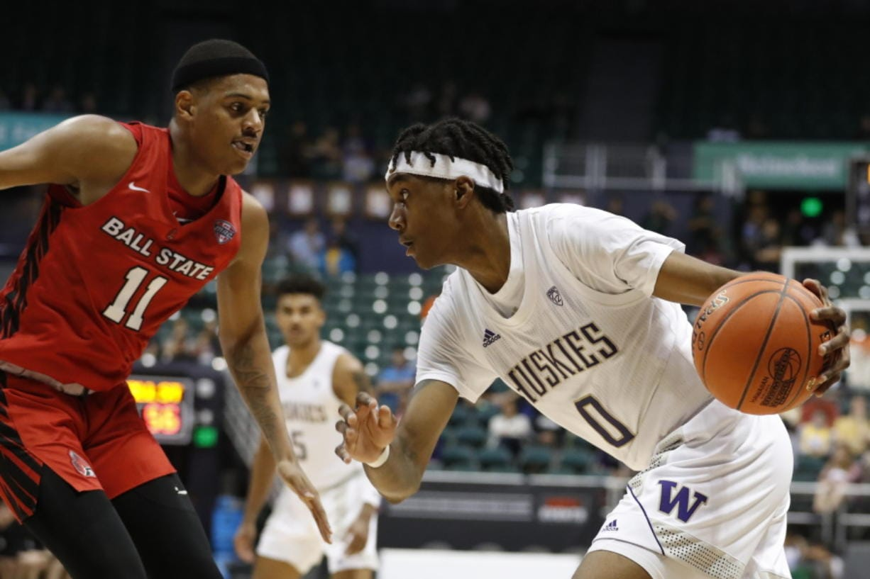 Washington forward Jayden McDaniels (0) goes toward the basket against Ball State guard Jarron Coleman (11) during the second half of an NCAA college basketball game, Sunday, Dec. 22, 2019, in Honolulu.