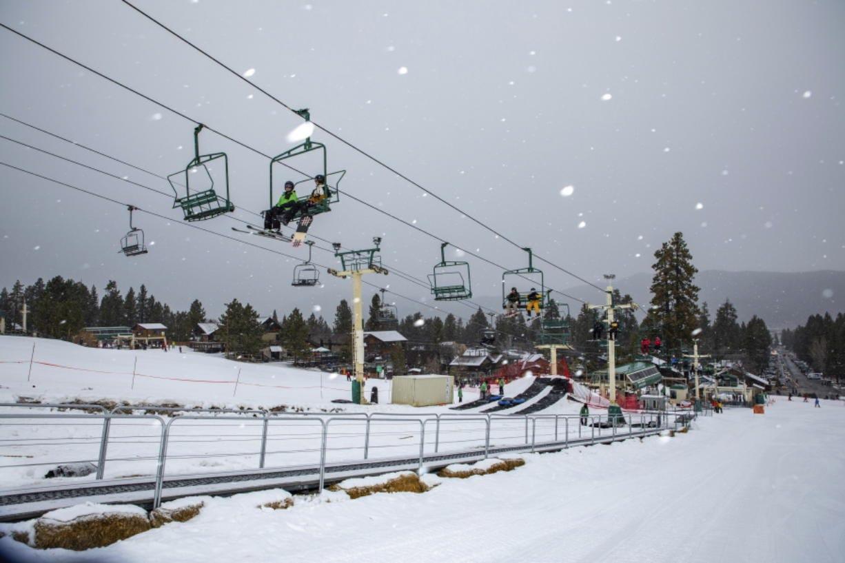 Snowboard and ski enthusiasts ride a lift to the slopes Monday at Big Bear Mountain Resort in Big Bear, Calif.