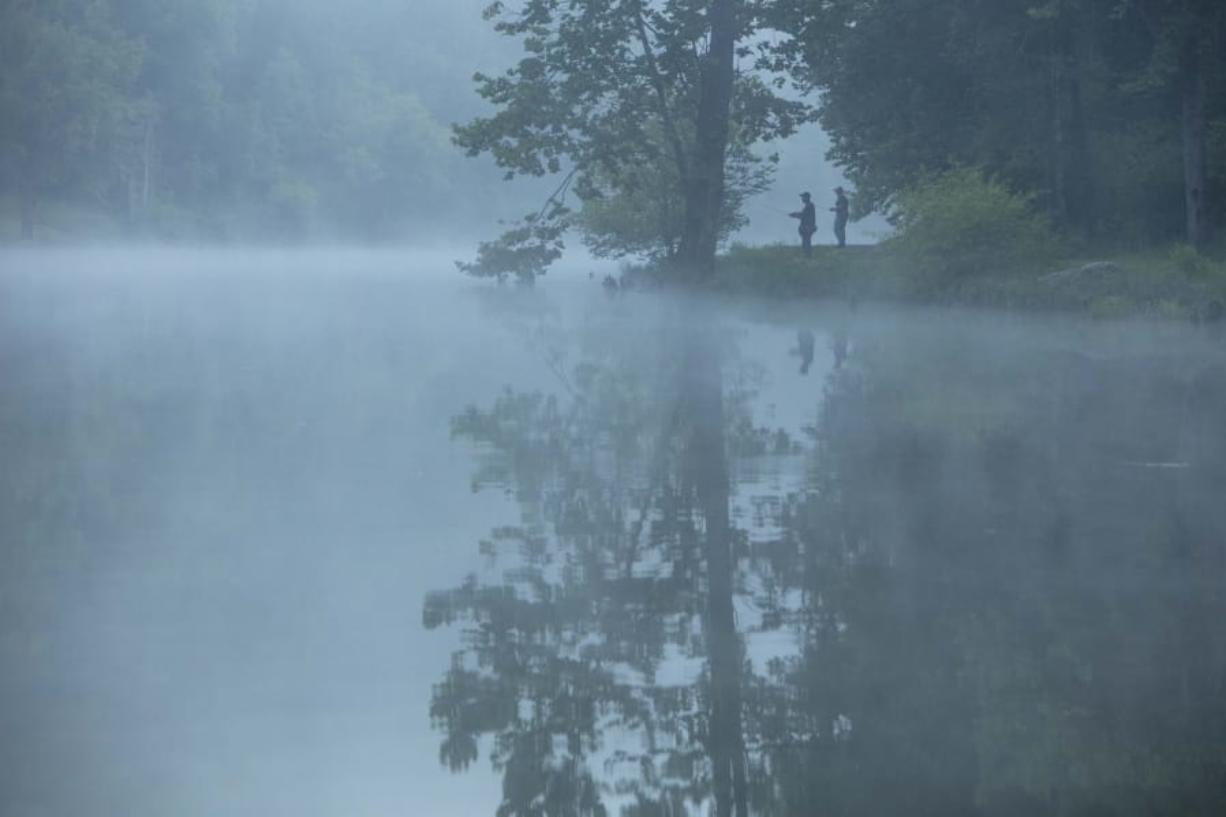 This July 26, 2019 photo provided by The Nature Conservancy shows two people fishing in the mist and fog over the Clinch River as seen from the Clinch Riverwalk on Sugar Hill property in St. Paul, Va. The Cumberland Forest Project protects 253,000 acres of Appalachian forest in Tennessee, Kentucky, and Virginia and is one of TNC's largest-ever conservation efforts in the eastern United States. (Travis Dove/The Nature Conservancy via AP) (Travis Dove/The Nature Conservancy)