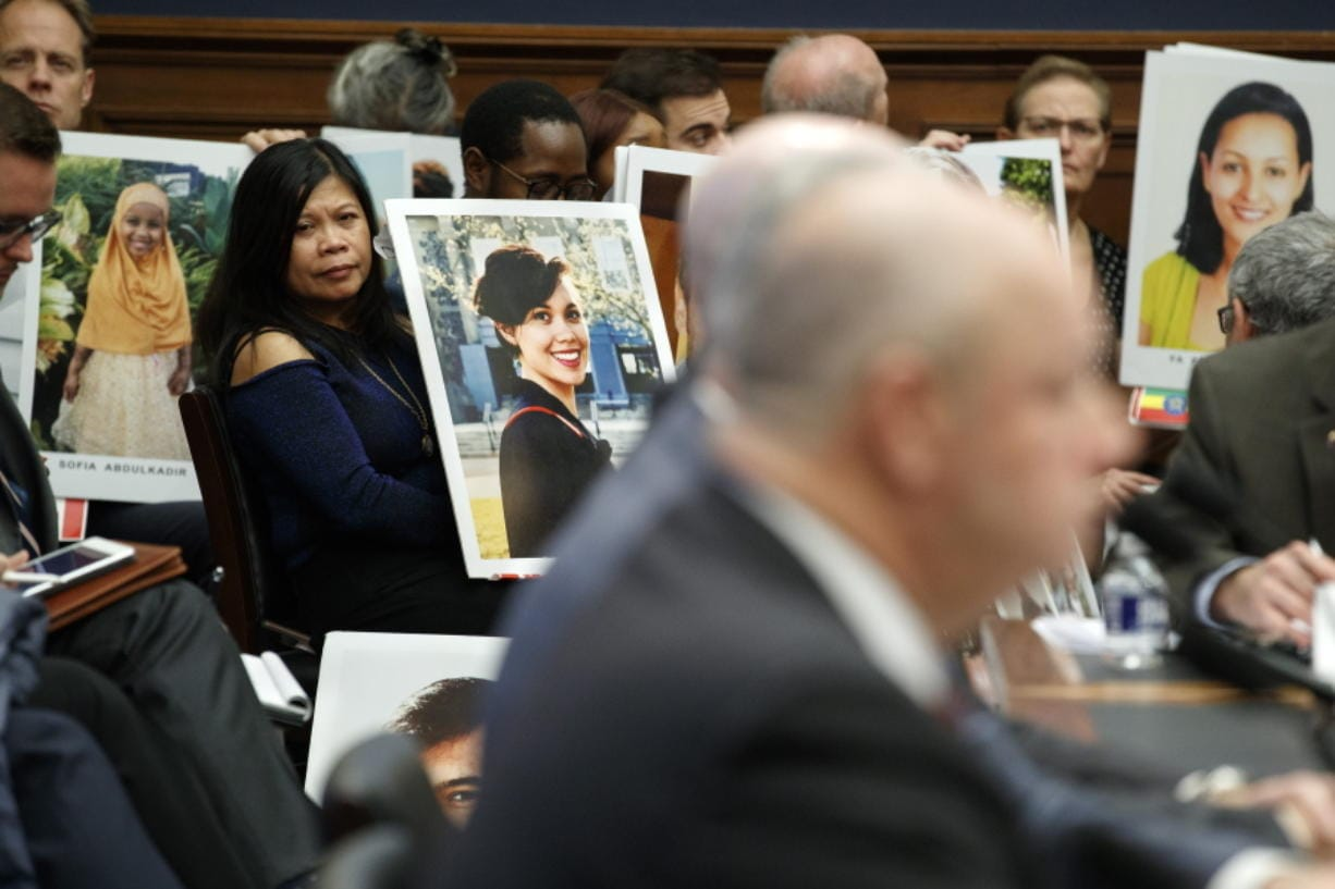 Family members of people who died in crashes of the Boeing 737 MAX hold photographs of their lost loved ones as FAA Administrator Stephen Dickson testifies during a House Transportation Committee hearing on the Boeing 737 MAX, Wednesday, Dec. 11, 2019, on Capitol Hill in Washington.