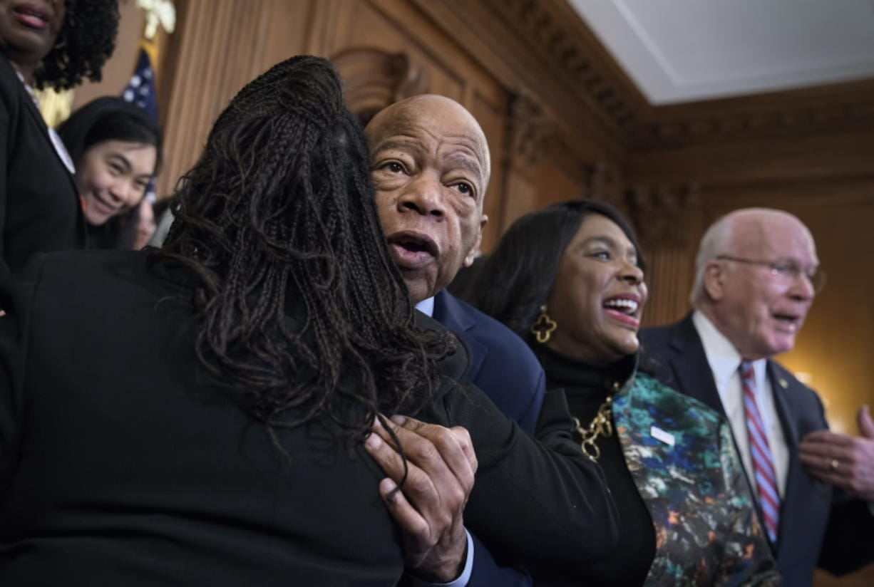 Civil rights leader Rep. John Lewis, D-Ga., is hugged as House Democrats gathered before passing the Voting Rights Advancement Act to eliminate potential state and local voter suppression laws, at the Capitol in Washington, Friday, Dec. 6, 2019. At right is Rep. Terri Sewell, D-Ala., who introduced the bill and who represents Selma, Ala., a city that was at the forefront of the 1960s civil rights movement. They are joined at far right by Sen. Patrick Leahy, D-Vt. (AP Photo/J.