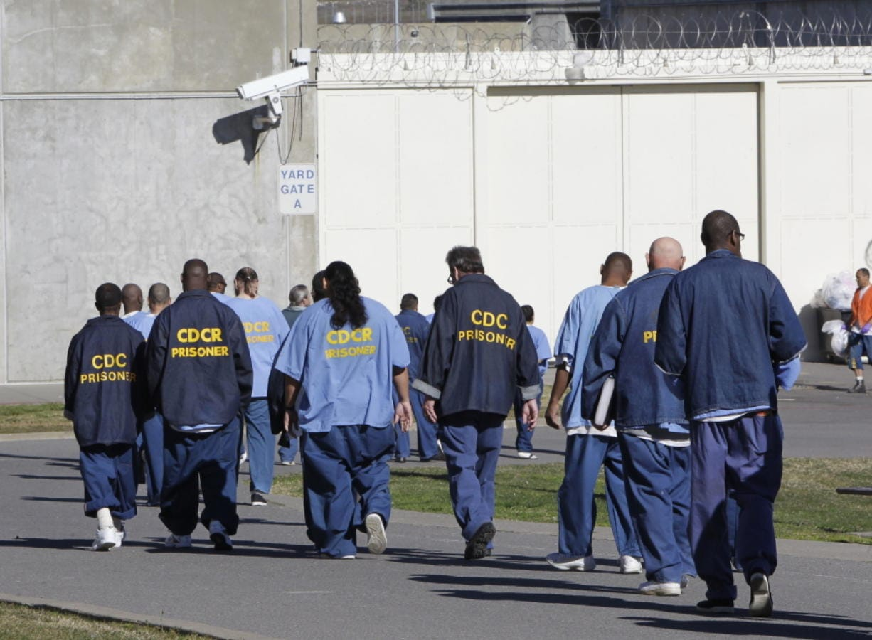 FILE - In this Feb. 26, 2013, file photo, inmates walk through the exercise yard at California State Prison Sacramento, near Folsom, Calif. Racial disparities have narrowed across the United States criminal justice system since 2000, though blacks remain significantly more likely to be impacted than whites, according to a study released Tuesday, Dec. 3, 2019, by the nonpartisan Council on Criminal Justice.