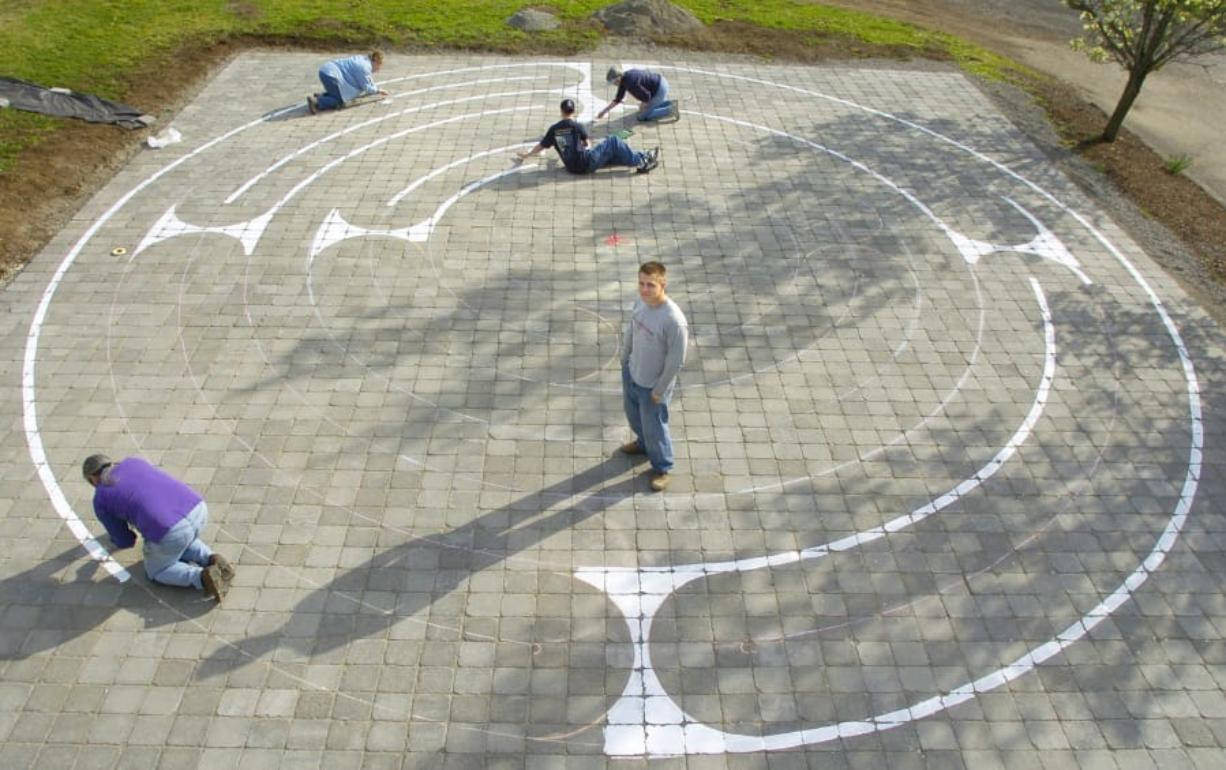 In this file photo from March 2005, Eagle Scout Peter Sterr, center, watches while friends and family paint a labyrinth pattern onto brick pavers at Beautiful Savior Lutheran Church in east Vancouver.