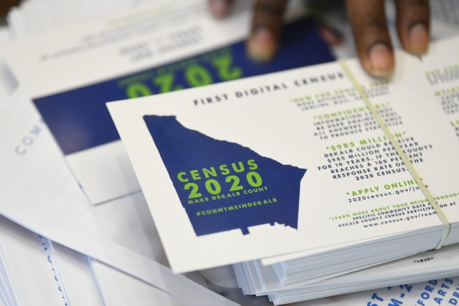 FILE - In this Aug. 13, 2019, file photo a worker gets ready to pass out instructions in how fill out the 2020 census during a town hall meeting in Lithonia, Ga. Facebook says it won't allow interference with the U.S. census on its platform, including posting misleading information about when and how to participate, who can participate and the consequences of taking part.