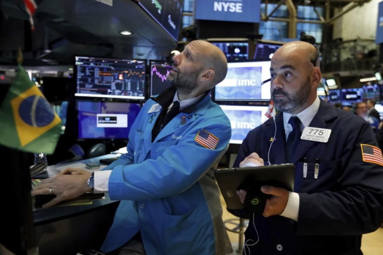 FILE - In this Nov. 15, 2019, file photo specialist Meric Greenbaum, left, and trader Fred DeMarco work on the floor of the New York Stock Exchange. The U.S. stock market opens at 9:30 a.m. EST on Friday, Dec. 6. (AP Photo/Richard Drew, File)